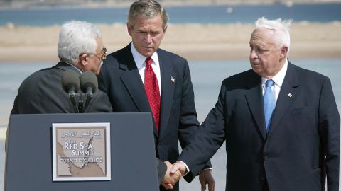"""In June 2003, Sharon, right, met with Palestinian Authority leader Mahmoud Abbas, left, and U.S. President George W. Bush to discuss a Middle East """"road map"""" for peace. After the meeting, Sharon expressed his """"strong support"""" for a two-state solution to the Israeli-Palestinian conflict."""