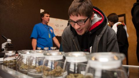 Tyler Williams of Blanchester, Ohio, looks over marijuana strains at the 3-D cannabis dispensary on January 1 in Denver, Colorado.