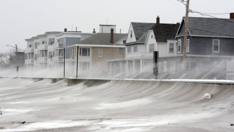 Winds whip snow from the beach across Winthrop Shore Drive in Winthrop, Massachusetts.