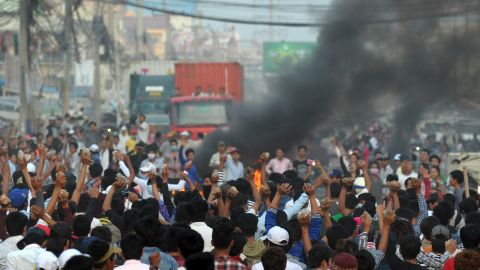 Cambodian garment workers carry rocks as they shout slogans after a brief clash with police during a protest outside a factory in the country's capital on Thursday.