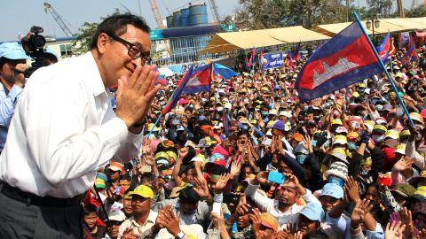 Leader of the opposition Cambodia National Rescue Party (CNRP) Sam Rainsy greets supporters during a demonstration in Phnom Penh on December 29, 2013.