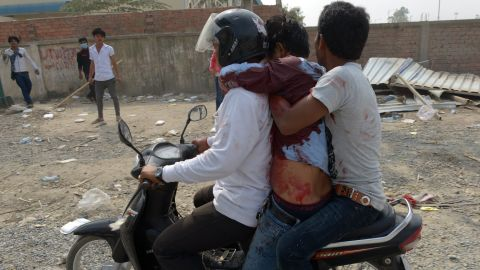 Cambodian workers transport a man who was injured during a confrontation with military police on Friday.