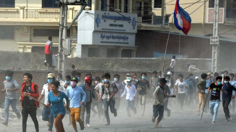 Cambodian protesters run from clashes with military police in Phnom Penh on January 3, after a week-long demonstration for better pay turned violent.