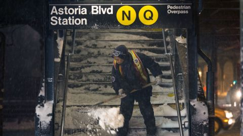 A worker clears snow from a subway station in Queens, New York, on January 3. Public schools were closed Friday after up to 7 inches of snow fell in New York City.