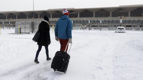 A couple walks across a snow-covered parking lot January 3 at Newark Liberty International Airport.