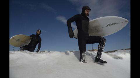 Surfers make their way through snow on New York's Rockaway Beach on January 3.