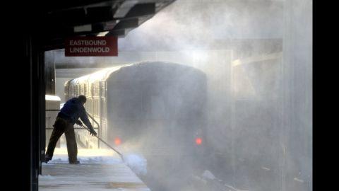 Blowing snow swirls as a worker shovels a platform at a Haddonfield, New Jersey, train station on January 3.