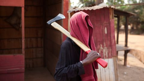 A member of an armed neighborhood defense squad, which residents say is local Christian residents protecting themselves, carries a machete as he walks near a roadblock in Bangui on Tuesday, December 31.