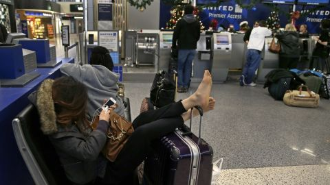 A woman props up her feet on her luggage January 6 after her flight home was canceled at Logan International Airport in Boston.