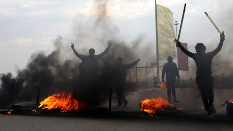 Iraqi Sunni masked protesters burn tires to blocked the main highway to Jordan and Syria, outside Fallujah, 40 miles (65 kilometers) west of Baghdad, Iraq, Monday, Dec. 30, 2013.