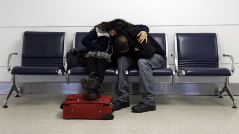 A man and woman do their best to get comfortable while stranded at Lambert-St. Louis International Airport on Sunday, January 5.