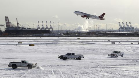A plane takes off from Newark Liberty International Airport in Newark, New Jersey, as trucks plow snow on the tarmac January 3.