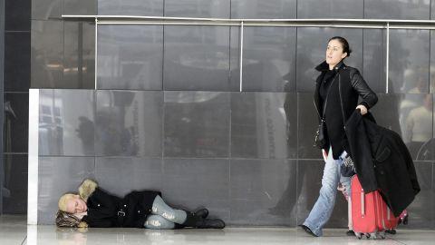 A woman sleeps on the floor of New York's JFK Airport on January 3.