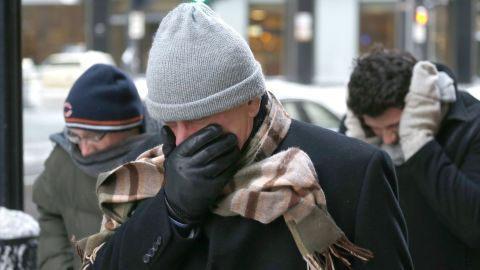Men battle the bitter wind as they walk in Chicago on January 6.