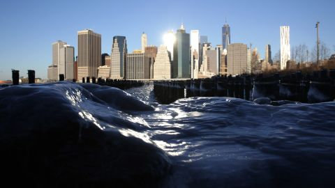 Ice forms around rocks on the Brooklyn waterfront, across from Lower Manhattan, on January 7, in New York City.