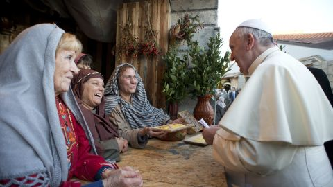 The Pope greats a group of women participating in the nativity scene.