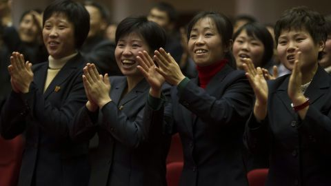 North Koreans applaud at the start of the game.