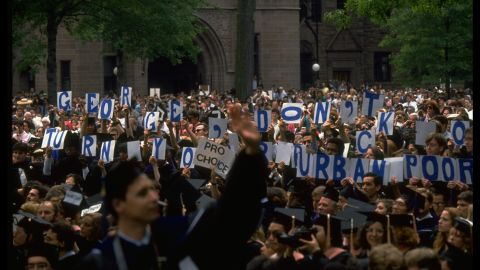 """During a 1991 commencement speech given by President George H. W. Bush at Yale University, attendees hold signs that read, """"George, don't turn your back on urban poor."""" Like Carter, Bush was more concerned with other issues during his presidency."""