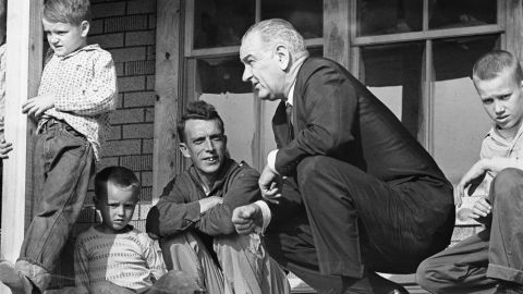 """U.S. President Lyndon B. Johnson visits a family in Inez, Kentucky, during a tour of poverty-stricken areas of the country in April 1964. Earlier that year, Johnson declared a """"war on poverty"""" in his State of the Union address. He then worked with Congress to pass more than 200 pieces of legislation, which included early education programs and social safety nets such as Medicare and Medicaid."""
