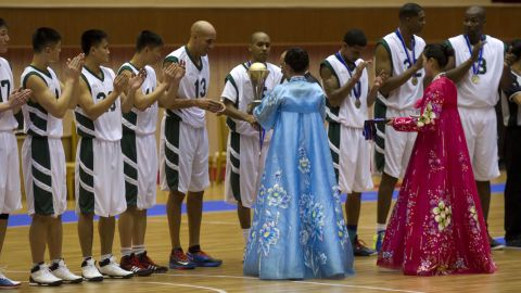 Doug Christie is handed a trophy as North Korean players applaud at the end of the game.