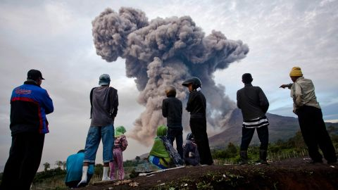 People watch as Mount Sinabung smokes.