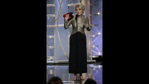 Actress Emma Thompson holds a martini in one hand and her shoes in the other while presenting an award.