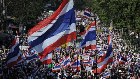 Thai anti-government protesters wave national flags as they march through the streets of Bangkok in a move to 'shut down' the city on January 13, 2014.
