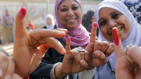 Egyptians women show their inked fingers after casting their votes at a polling station in Cairo, Egypt, Tuesday, Jan. 14, 2014.