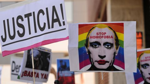 A protester holds up an image of Putin wearing lipstick in Madrid in 2013.