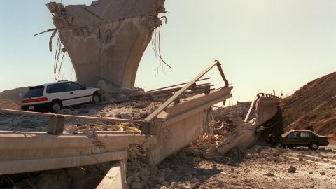 Cars lie smashed by the collapsed Interstate 5 connector few hours after Northridge earthquake, on January 17, 1994, in Sylmar, California. Federal officials are still trying to measure the amount of damage from the earthquake and said freeways suffered at least $100 million in damage. The Northridge earthquake occurred on January 17, 1994 at 4:31 AM Pacific Standard Time in Reseda, a neighborhood in the city of Los Angeles, California.        (Photo credit should read JONATHAN NOUROK/AFP/Getty Images)