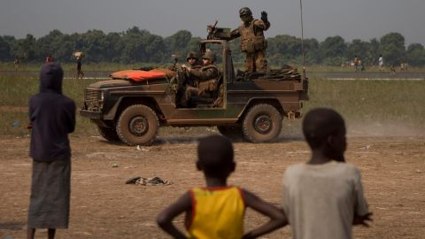 A French soldier waves to children as his jeep patrols the area between an airstrip and a makeshift displacement camp at M'Poko International Airport on January 9.