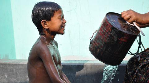 A young boy takes a bath at a public water stand post near Uttar Bishli, Bangladesh.