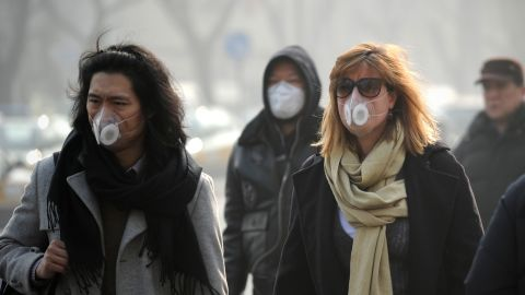 """People use face masks during their commute in Beijing on January 16. The Chinese government is trying to control the number of new vehicle registrations this year in some cities to help improve air quality, <a href=""""http://money.cnn.com/2014/01/20/autos/china-autos-pollution/"""">CNNMoney reports</a>."""