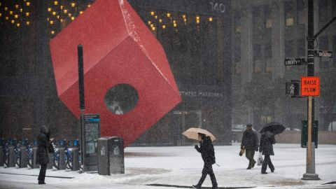 """People walk past the art installation """"Red Cube"""" by Isamu Noguchi in New York during a snow storm on January 21."""