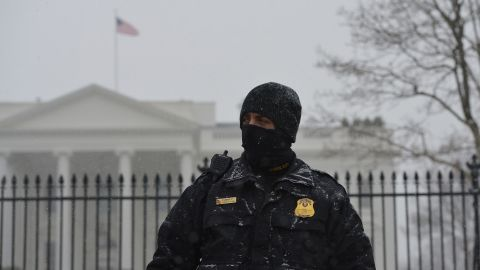 A member of the Secret Service Uniform Division stands guard in front of the White House as snow falls in Washington on January 21.