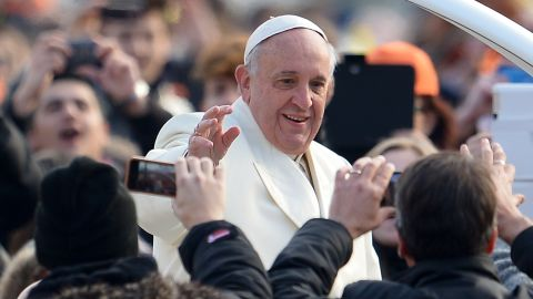 Pope Francis salutes the crowd as he arrives for his weekly general audience in St Peter's square at the Vatican on January 15, 2014. AFP PHOTO / VINCENZO PINTO (Photo credit should read VINCENZO PINTO/AFP/Getty Images)