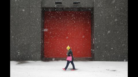 A woman walks in Baltimore as snow falls Tuesday, January 21.