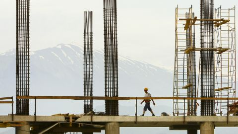 A construction worker walks on the top of the building site of the Bolshoi Ice Palace in Sochi in June 2010.