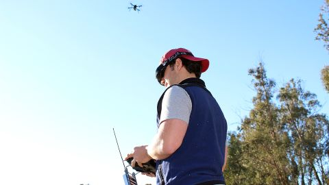 """<a href=""""http://3drobotics.com/"""" target=""""_blank"""" target=""""_blank"""">3D Robotics</a> employee Pablo Lema views live video streamed from the drone above his head. The first-person view is displayed on his goggles, while he steers the device with a hand-held controller."""