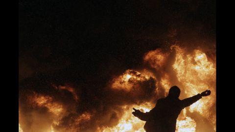A protester throws a stone in front of a plume of fire and smoke during clashes with police in central Kiev.