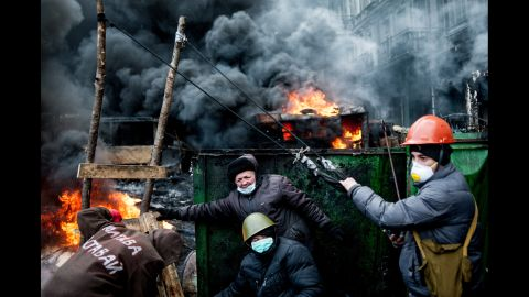Ukrainian protesters use a huge catapult to throw stones at riot police as tires burn in Kiev on Thursday, January 23.