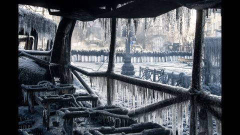 Riot police stand guard near a burnt-out bus covered in icicles in Kiev on January 23.