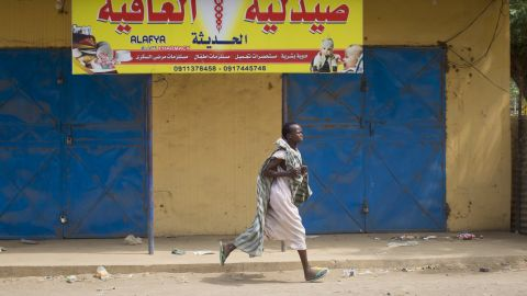 A woman runs through the street in Malakal as gunshots ring out a few streets over on January 21.