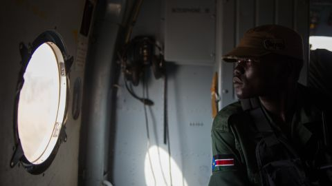 A Sudan People's Liberation Army soldier sits in a helicopter flying over Western Equatoria State on Tuesday, January 14.