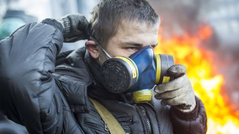 A protester puts on a gas mask near Dynamo Stadium in Kiev on January 24.