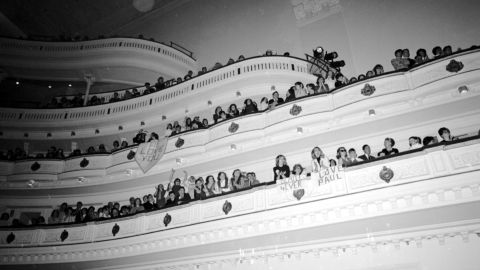 Fans cheer for The Beatles and hold signs of encouragement during the band's concert at Carnegie Hall on February 12, 1964, in New York.