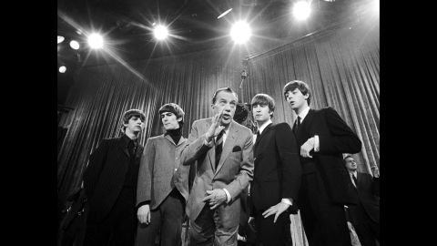 """Television host Ed Sullivan, center, stands with The Beatles on February 9, 1964, during a rehearsal for the band's appearance on """"The Ed Sullivan Show."""" The iconic television appearance remains one of the highest-rated nonsports programs of all time. Nielsen estimated that 45% of the country watched the show -- more than 73 million people then."""