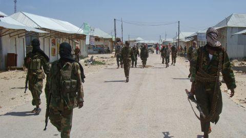 Al-Qaeda linked al-shabab recruits walk down a street on March 5, 2012 in the Deniile district of Somalian capital, Mogadishu, following their graduation.