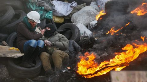A couple try to keep warm near a fire at a barricade in Kiev on January 27.