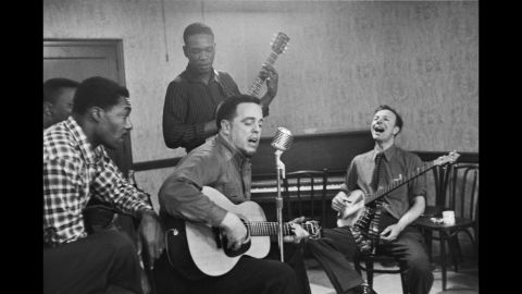 Musician Alan Lomax, center, and Seeger sing and play instruments as they practice for a concert in 1959.